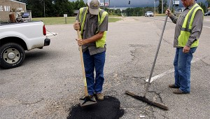 Photo by Cassandra Favre Herman Boutwell and Greg Malley used permapatch to repair a pothole on Highway 11 North on Tuesday. Patching potholes is one of the many jobs that road crews attend to on a daily basis.