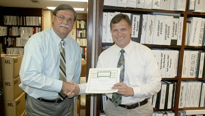 RECOGNITION: From left, Poplarville School District Superintendent Carl Merrit presented Poplarville High School Principal Jon Will with a certificate recognizing the school for receiving a bronze award with the U.S. News and World Reports. Photo by Jeremy Pittari