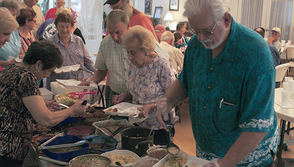 Senior citizens line up to eat a nutritious meal consisting of a wide variety of food at the Senior Center in Picayune. This is part of their Pot Luck Lunch they hold at the center every other Friday.