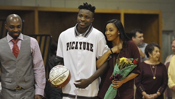 Stephane Ayangma walks to center court during Picayune's senior night with his brother Eric, pictured left, and his sisten in-law, pictured right. Photo by Taylor Welsh